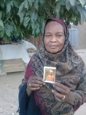 Hajja Gana Suleiman shows a photograph of her son