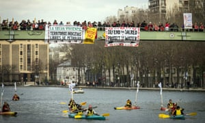 Indigenous people paddle down the Seine as others stand on a bridge holding banners during a rally in Paris demanding Indigenous rights are included in the climate accord on December 6, 2015 on the sidelines of the COP21 climate change conference. / AFP / LIONEL BONAVENTURELIONEL BONAVENTURE/AFP/Getty Images
