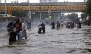 People make their way through flooded streets after a heavy downpour in Karachi on Thursday.