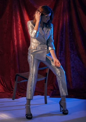 Sharon Horgan in a silver suit, perched on the back of a chair, looking down and away