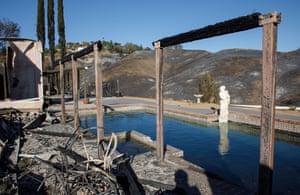 A statue and swimming pool survive the flames that consumed a home along Dapplegray Road after the Woolsey Fire burned through Bell Canyon