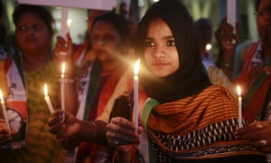 Activists of the Nationalist Congress Party hold lighted candles during a protest in Mumbai, India