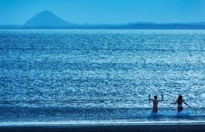 Edinburgh, UK Dawn swimmers on Portobello Beach in the Firth of Forth, with North Berwick Law on the horizon