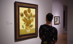 A woman looks at the Sunflowers painting.