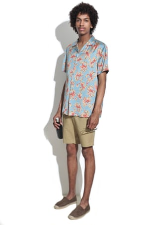 Man wearing floral shirt and sand shorts