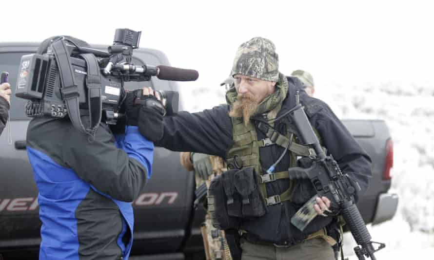 """A man standing guard pushes a videographer aside after members of the """"3% of Idaho"""" group along with several other organizations arrived at the Malheur National Wildlife Refuge near Burns, Ore., on Saturday, Jan. 9, 2016. A small, armed group has been occupying the remote national wildlife refuge in Oregon for a week to protest federal land use policies. (AP Photo/Rick Bowmer)"""