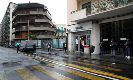Shoppers queue up in the rain in Sicily.