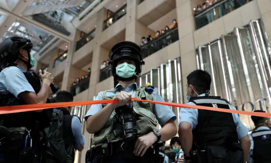 Police set up a cordon and search people during a rally at a shopping mall in Hong Kong