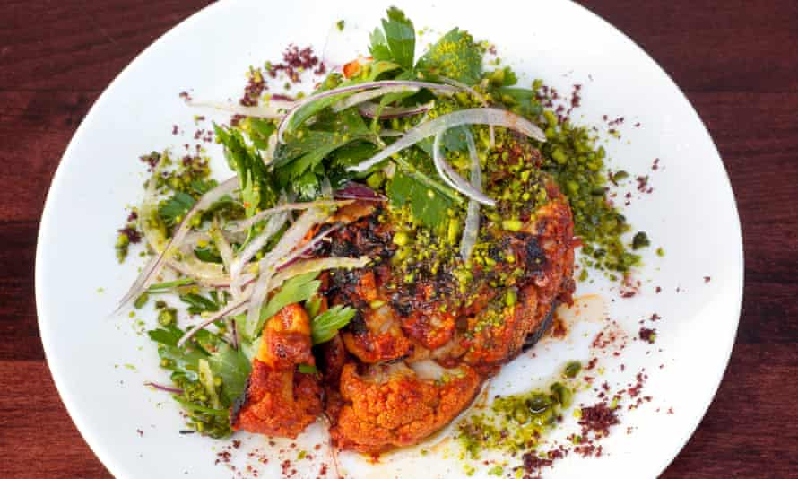 Roast cauliflower 'slathered with red onions, parsley and pistachios' on a plate