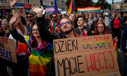 A crowd of people march with rainbow flags and colourful signs