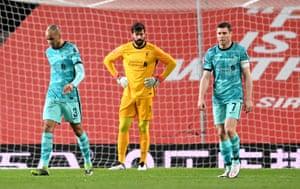James Milner, Fabinho and Alisson Becker of Liverpool look dejected.