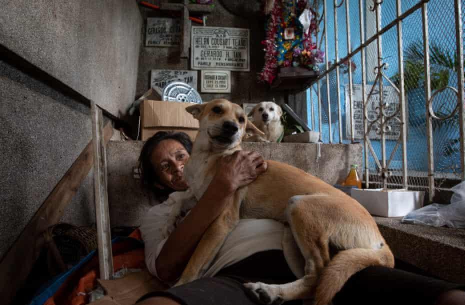 زنی با سگ خود بازی می کند.  برخی از خانواده ها نسلها در گورستان زندگی کرده اند