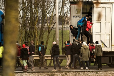 Refugees clamber into the back of a lorry in Calais