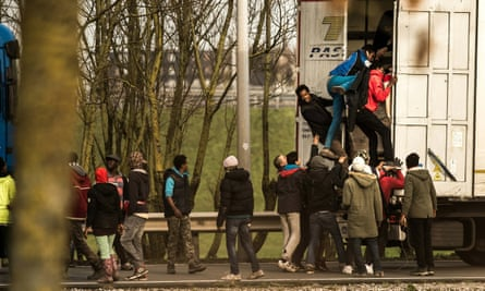 People climb into the trailer of a lorry queueing at the Eurotunnel in Calais.