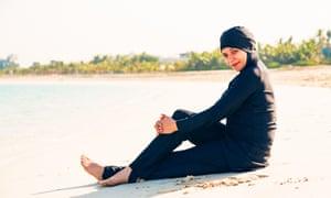 A woman wearing a burkini on the beach