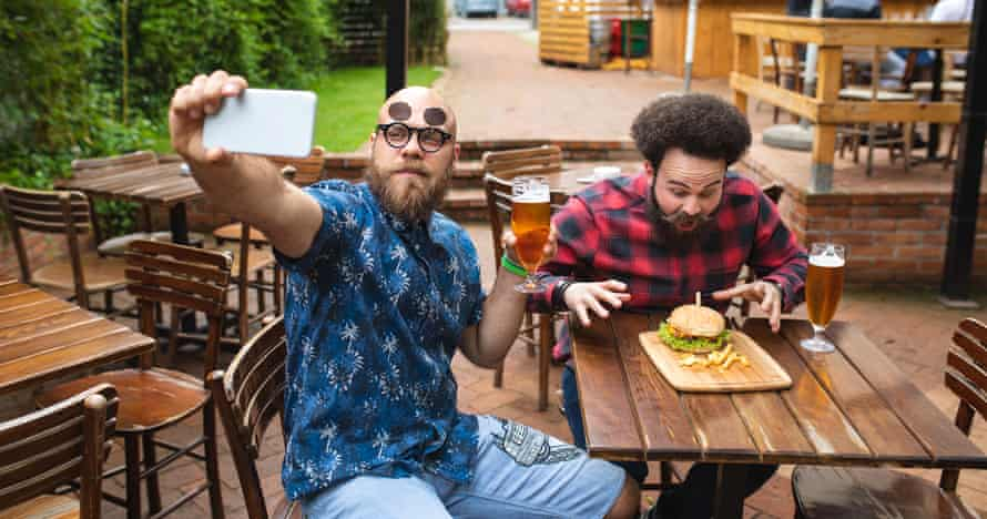 A stock image showing two men posing for a selfie while showing off food and beer