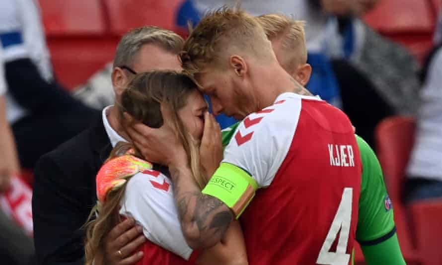 Simon Kjær consoles Christian Eriksen's wife, Sabrina Kvist, after the Internazionale player collapsed on the pitch during the game against Finland.