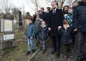 President Emmanuel Macron holds children by the hands as he walks past graves vandalised with swastikas during a visit to the Jewish cemetery. Around 80 graves have been vandalised in the Alsace village close to the German border. Quatzenheim, France