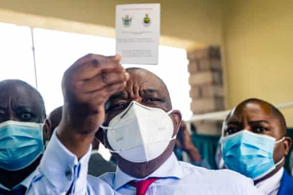 Zimbabwe vice president and minister of health Constantino Chiwenga holds up his vaccination certificate after receiving his first shot of Sinopharm, 18 February 2021