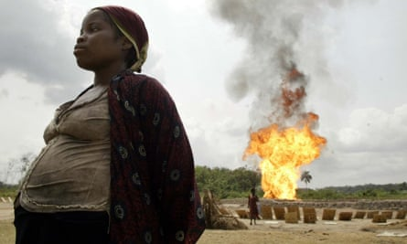 A gas flare is seen in the background as a pregnant woman dries tapioca near Utorogu flow station in Warri, Nigeria