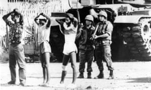 US soldiers stand guard over Grenadian prisoners in St George's, Grenada, 1983.