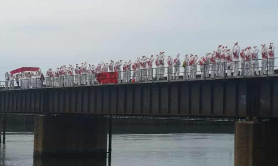 Protesters dressed in white overalls block the coal line that connects the coalmines in the Hunter Valley with the port at Sandgate in Newcastle on Sunday.