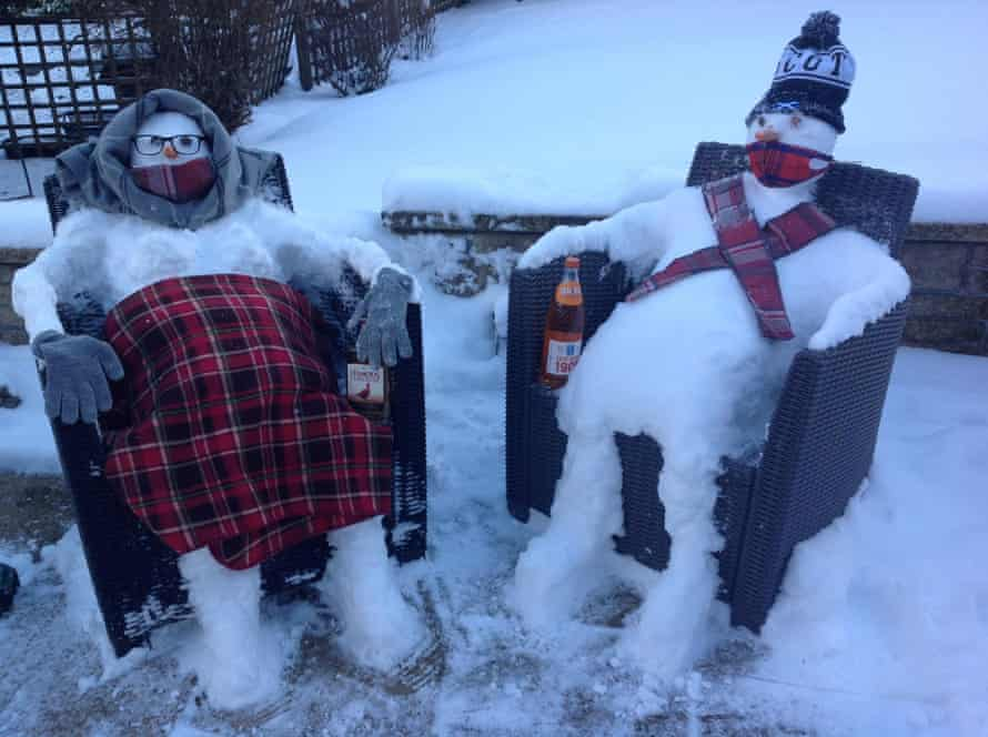 Two snowmen sitting in chairs