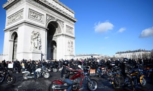 Motorcyclists ride past the Arc de Triomphe as they pay tribute to Hallyday