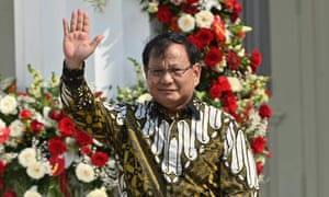 Prabowo Subianto gestures towards journalists as President Joko Widodo unveils his new cabinet on the steps of the Merdeka Palace in Jakarta