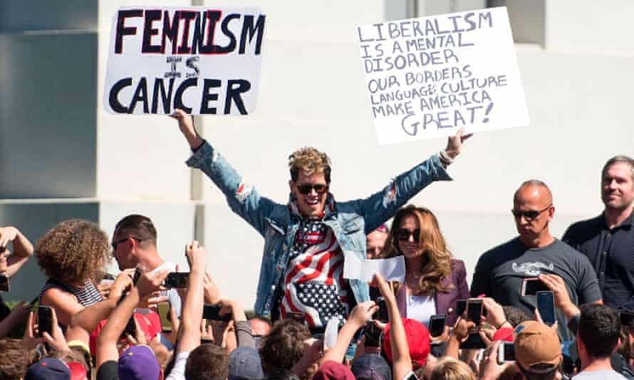 Milo Yiannopoulos holds up signs to a crowd of supporters on the University of California, Berkeley that read: 'Feminism is cancer' and 'Liberalism is a mental disorder ...'