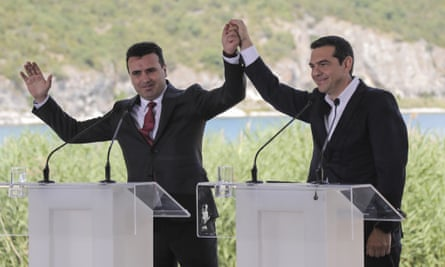 Zoran Zaev and Alexis Tsipras raise their hands during the signing ceremony at lake Prespa.