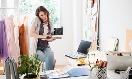 Female fashion designer in her office, on the phone and juggling paperwor