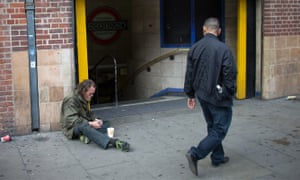 A man begs on a street in London, England.