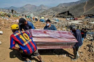 Relatives carry the plastic-wrapped coffin of a suspected Covid-19 victim at the Nueva Esperanza cemetery, one of the largest in Latin America, in the southern outskirts of Lima, Peru