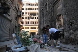 Two men clear debris from a street in west Aleppo