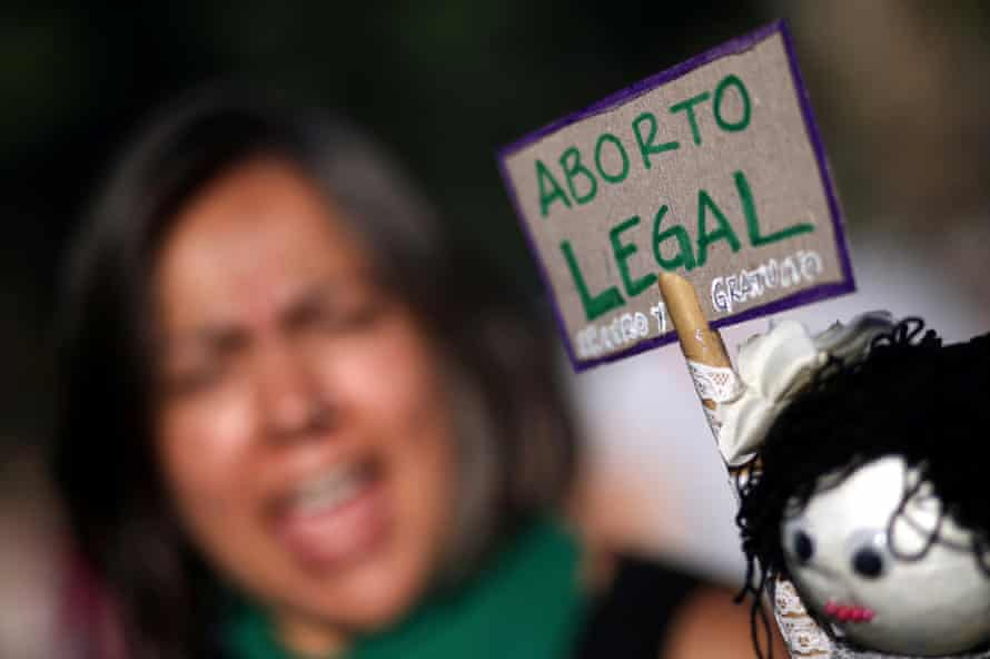 A woman protests next to a sign that reads 'Legal abortion'