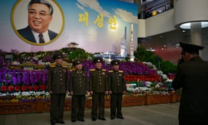 Military personnel pose next to a portrait of Kim Il-sung on Wednesday in Pyongyang, North Korea, ahead of birthday celebrations for the founding leader.