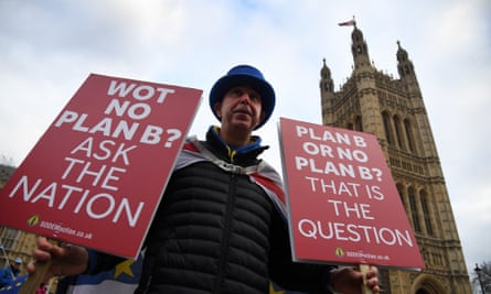 A man holds signs reading 'Plan B or no Plan B? That is the question' outside parliament.