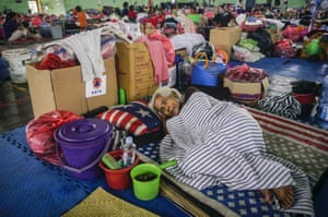An elderly lady evacuated from her village, rests at the Klungkung evacuation shelter surrounded by her belongings
