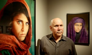 Steve McCurry poses next to his photos of Sharbat Gula, the 'Afghan Girl', in 2013.