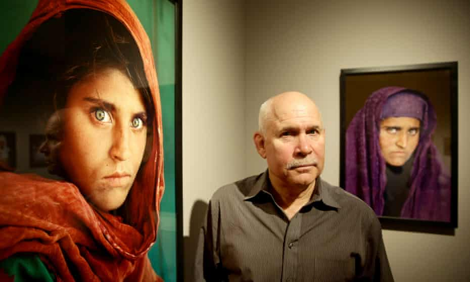 Steve McCurry next to Afghan Girl, 1984, with his portrait of Sharbat Gula, taken nearly two decades later, in the background.
