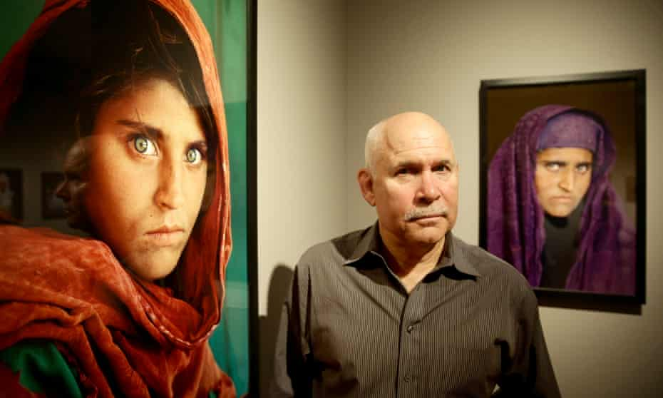 Photographer Steve McCurry with his photos of Sharbut Gula, the 'Afghan Girl' at the opening of his Overwhelmed by Life exhibition in 2013.