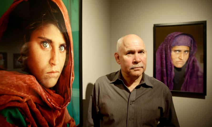 Photographer Steve McCurry next to his photos of Sharbat Gula at an exhibition in Hamburg, Germany, in 2013.