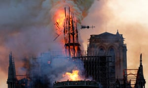 The spire of Notre Dame collapses, as smoke and flames engulf the cathedral.