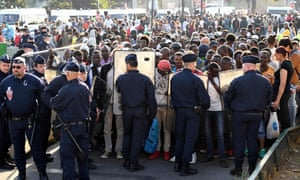 French riot police officers stand guard during the clearing of a makeshift camp on Friday.