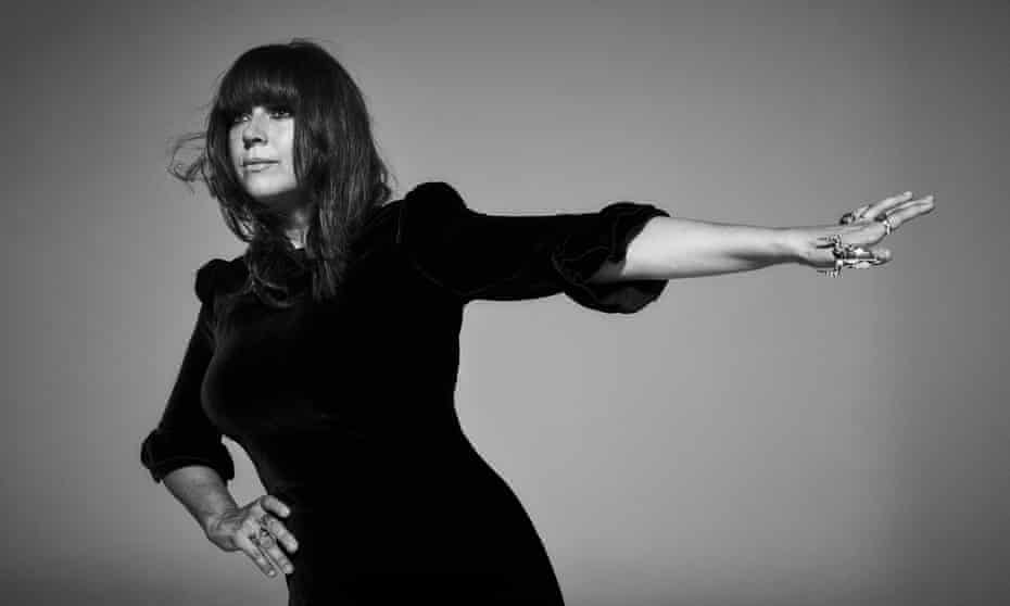 Cat Power  in a black velvet dress, long black hair and one arm reaching out, multiple chunky silver rings on her fingers