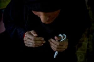Fatima, 80, fingers her prayer beads in her shelter in Zahle, Lebanon