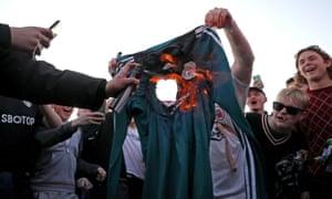 A supporter burns a Liverpool shirt outside Elland Road.