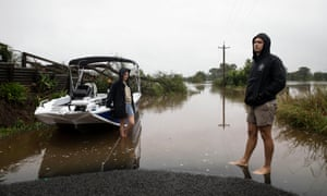 Locals Demie Prichard and Brewer Lynch take a friend's boat to inspect houses along the Hawkesbury River area, Pitt Town, NSW on 23 March 2021.
