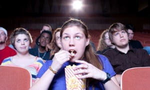 A girl eating popcorn at the cinema